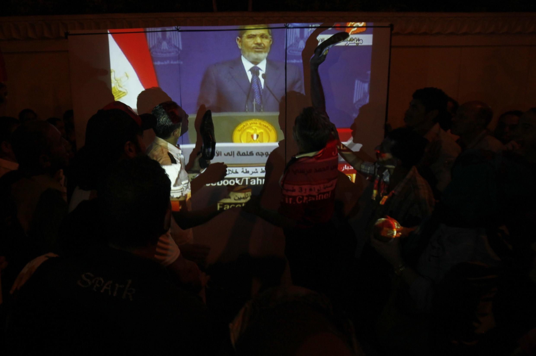 Des manifestants protestent devant le ministère égyptien de la Défense, et visent l'écran avec leurs chaussures, pendant le discours du président Morsi le 26 juin 2013