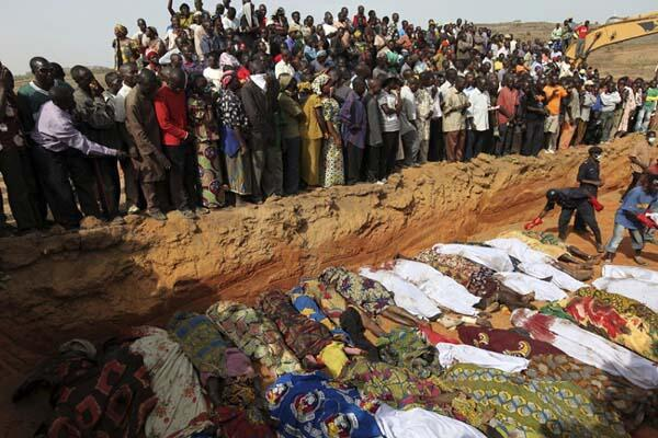 Villagers look at bodies of victims of religious attacks lying in a mass grave outside Jos on March 8, 2010