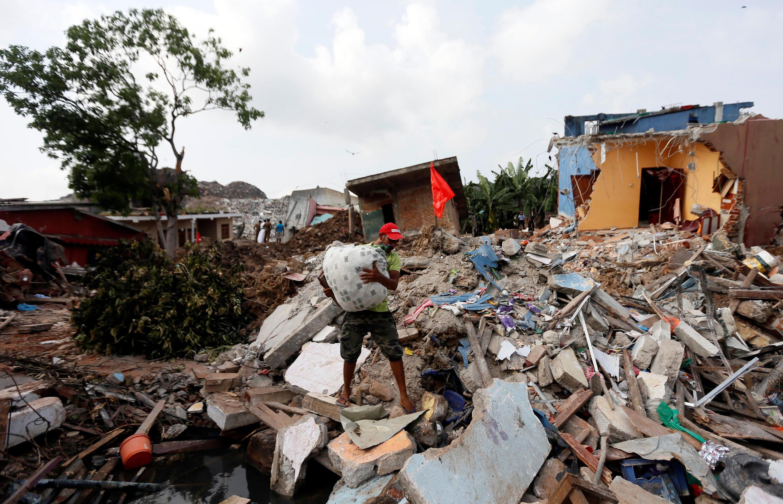 Un habitant d'un des bidonvilles qui entourent la décharge à ciel ouvert récupère quelque biens après l'effondrement de sa maison.
