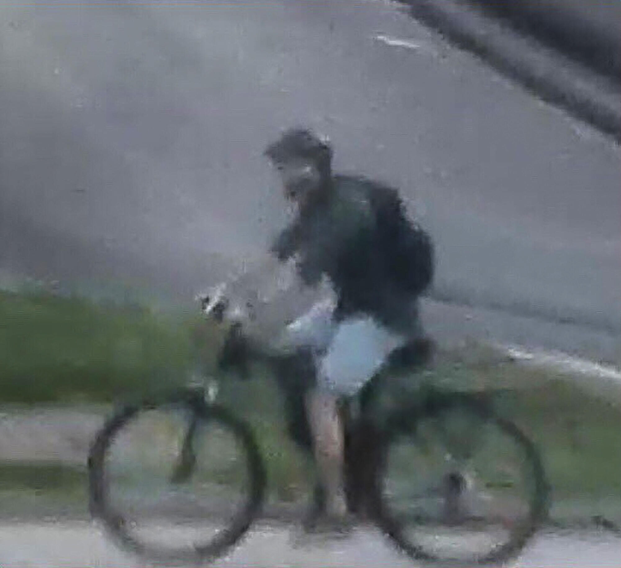 Video frame grab from a surveillance camera made available by the French Police on their Twitter account, showing a man riding a bike near the package bomb blast in Lyon.