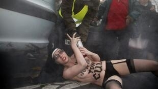 A topless activist of feminist movement Femen is evacuated by security personnel from a demonstration against sex-sex marriage.