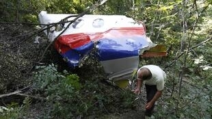 Homem passa ao lado de pedaço do Boeing da Malaysia Airlines acidentado no leste da Ucrânia.