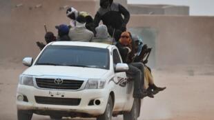 Une camionnette transportant des migrants passe à Agadez au Niger. Les passagers s'accrochent aux bâtons attachés au camion, à ne pas tomber en roulant dans le désert.