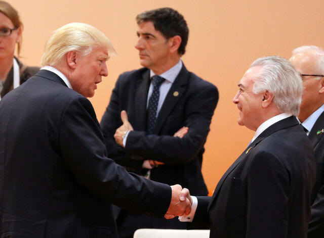 O presidente americano, Donald Trump (esq.), cumprimenta Michel Temer com seu famoso aperto de mão na sessão de trabalho deste sábado (8) na cúpula do G20, em Hamburgo.