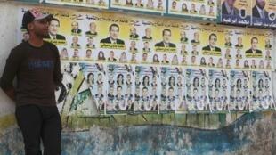 Jovem diante de muro com cartazes dos partidos islâmicos.