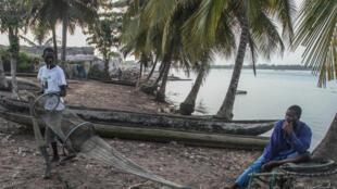 Lamine Sagna (g.), un pêcheur de crevettes qui vit sur la bande de terre de Grand Lahou, en Côte d'Ivoire, a dû déménager sa maison plusieurs fois pour fuir devant l'océan, qui gagne chaque année plus de terrain.