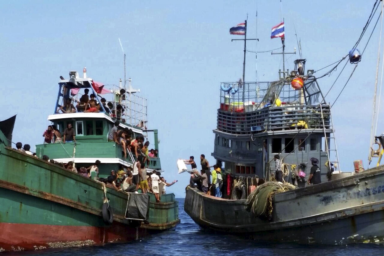 Pescadores tailandeses arrojan agua y comida a un barco rechazado por las autoridades tailandesas el 14 de mayo de 2015.