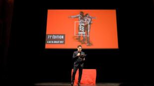 Olivier Py, le directeur du Festival d'Avignon, lors de la présentation de la programmation 2017 sous le « rouge rapide » de l'affiche officielle créée par le peintre Ronan Barrot.