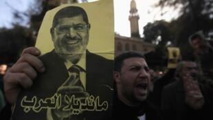 Manifestante egípcio carrega cartaz com foto do presidente destituído Mohamed Mursi, durante manifestação no Cairo, no dia 27 de dezembro de 2013.