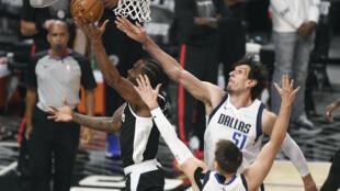 Kawhi Leonard, de Los Angeles Clippers, anota ante los jugadores de Mavericks Luka Doncic y Boban Marjanovic.