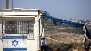 An Israeli woman leans on the guard post at the Migron outpost near the West Bank city of Ramallah
