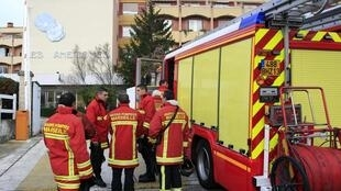 Firefighters stand in front of the retirement home where six women died