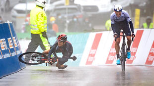 Down and out: Geraint Thomas falls at the end of the fifth stage of the Tour de Romandie