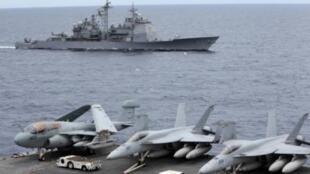 Các chiến đấu cơ Hoa Kỳ trên chiếc hàng không mẫu hạm USS George Washington, ngoài xa là tuần dương hạm USS Cowpens, trong chuyến thăm hữu nghị các nước tại vùng Biển Đông. Ảnh chụp ngày 3/9/2010.