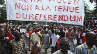 Des manifestants tiennent une banderole «Non au référendum».