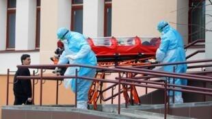 Медицинские работники переносят капсулу с женщиной, у которой заподозрен COVID-19, из общежития в Минске. 12.03.2020