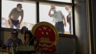 À Hong Kong, des ouvriers installent l'emblème chinois sur le fronton de l'hôtel Metropark où sont situés les locaux du bureau de sécurité nationale, le 8 juillet 2020.