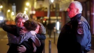 Pessoas se abraçam em frente ao Bataclan, onde mais de 100 pessoas morreram