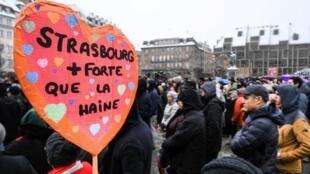 """Mulher segura cartaz mostrando a frase """"Estrasburgo mais forte que o ódio"""" durante homenagem às vítimas do atentado da última terça-feira (11), 16/12/2018"""