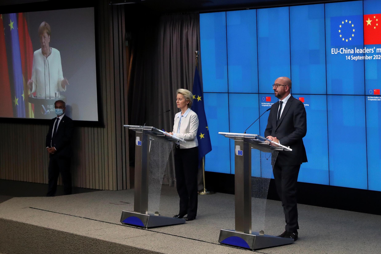 Chủ tịch Hội Đồng Châu Âu Charles Michel (P) và chủ tịch Ủy Ban Châu Âu Ursula von der Leyen, cùng thủ tướng Đức Angela Merkel (trên màn hình) họp báo sau thượng đỉnh Liên Âu- Trung Quốc, ngày 14/09/2020.