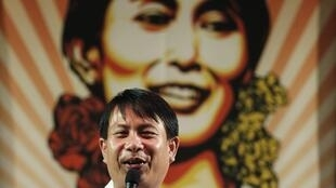 An activist sings in front of a portrait of Aung San Suu Kyi during an event celebrating her birthday, 20 June