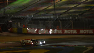 Kazuki Nakajima drives his Toyota through the night in front of the empty stands at Le Mans