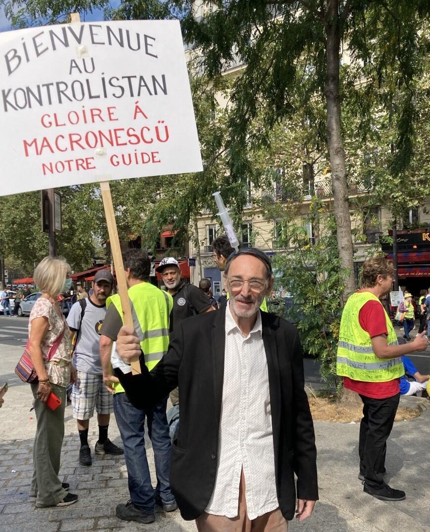 "Maurice holds a banner reading: ""Welcome to Kontrolistan, glory to Macronescu""."
