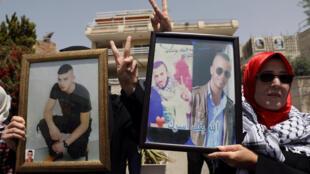 Palestinos com fotos de familiares presos, durante manifestação em solidariedade aos prisioneiros palestinos em greve de fome nas prisões israelenses. Jerusalém Oriental, 27 de abril de 2017.