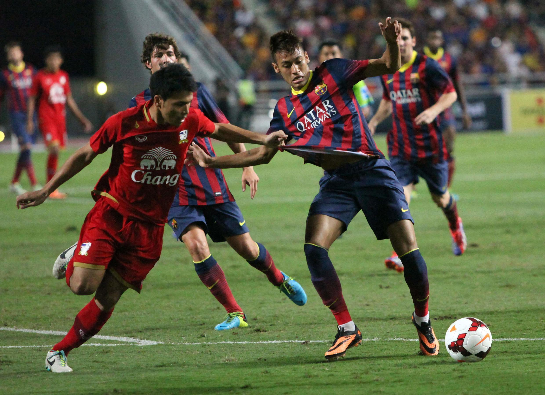 Dan wasan Barcelona Neymar yana taka kwallo a wasansu da Thailand a birnin Bangkok