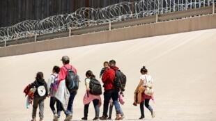 Migrantes caminham depois de atravessar o rio Bravo na fronteira entre Ciudad Juarez, no México, e El Paso, no Texas, EUA, visto de Ciudad Juarez, México, 9 de maio de 2019.