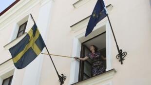 Une employée de l'ambassade de Suède à Minsk réarrange le drapeau national sur la façade.