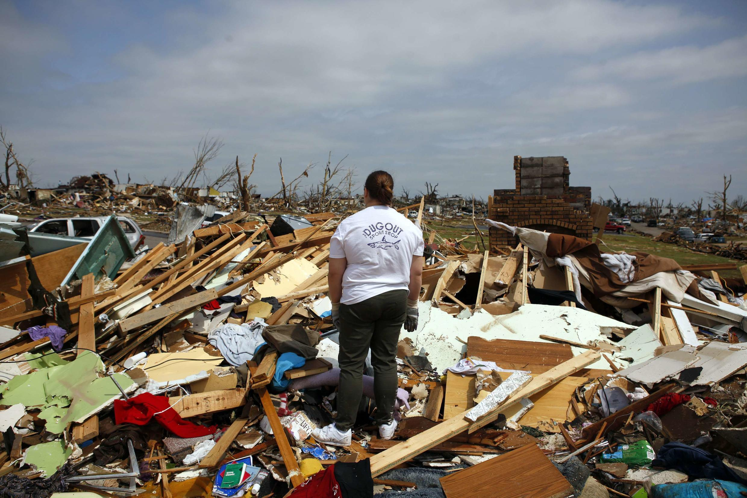 A woman looks out of her destroyed home in Joplin, Missouri