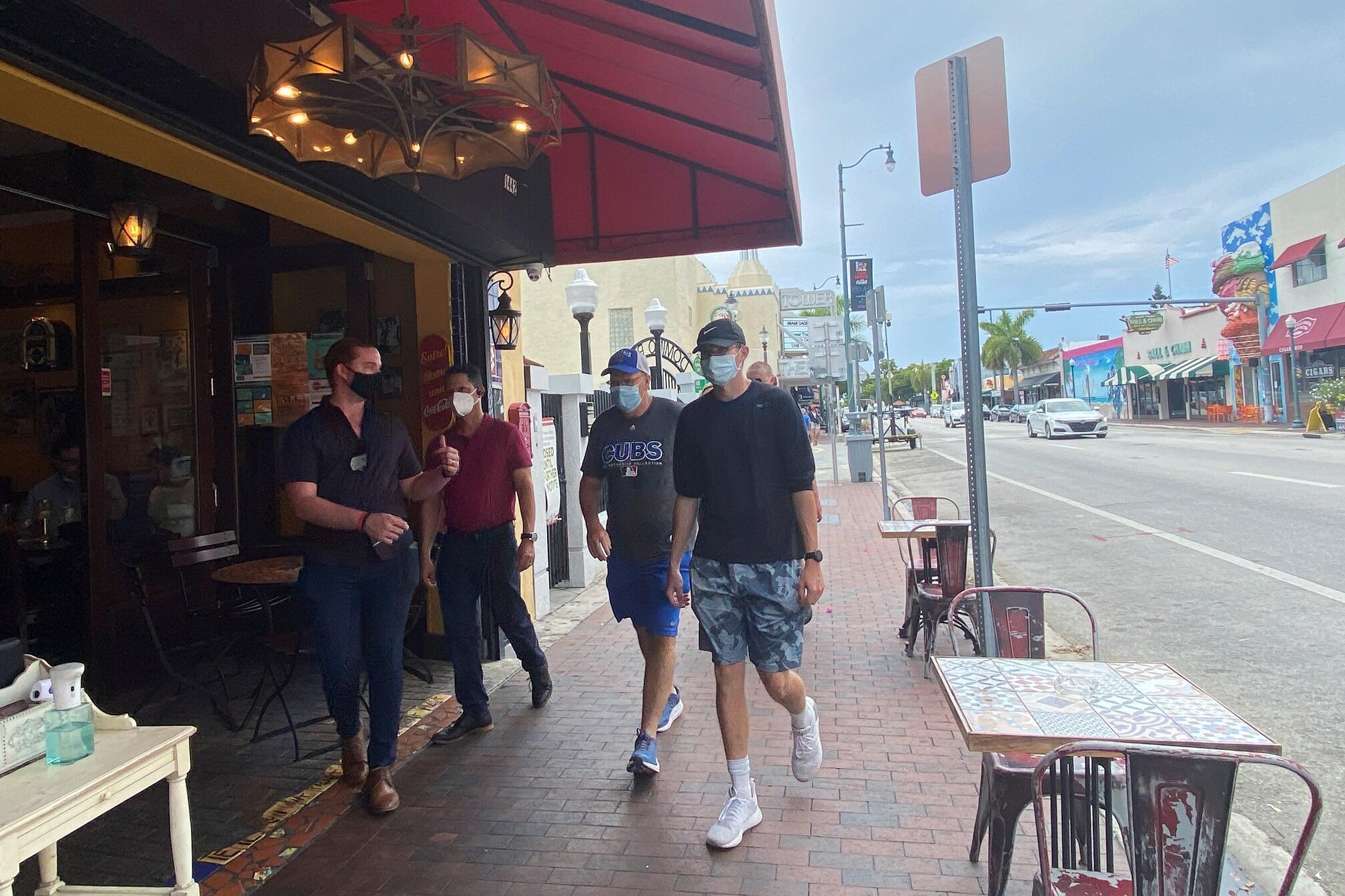 Port du masque et gel hydroalcoolique à disposition devant un bar du quartier Little Havana, à Miami, le 6 juillet 2020, en raison du Covid-19.