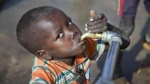 A child drinks from a water tap in northern Darfur