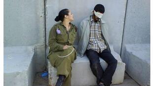 La soldate israélienne Eden Abergil pose près d'un détenu palestinien menotté et bandé, en 2008.
