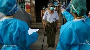 Tournée de tests de températures pour lutter contre le coronavirus en porte-à-porte avec les résidents de Rangoun, le 17 mai 2020.