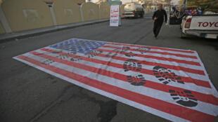 Cờ Mỹ được trải trên mặt đường ở Badgad ngày 03/01/2020 để cho xe giẫm qua sau cái chết của tướng Iran Qassem Soleimani.