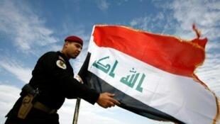 Askari polisi wa Iraq mbele ya bendera ya Iraq, katika mji wa Najaf Januari 9, 2016.