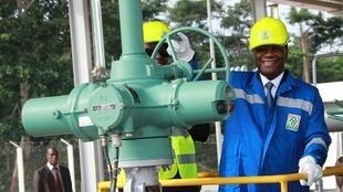 Le président ivoirien Alassane Ouattara ouvre une valve lors du lancement du pipeline qui reliera Yamoussoukro à Abidjan, le 29 juillet 2013, à Yamoussoukro.