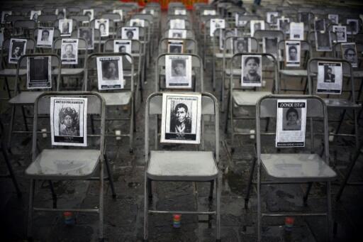 Fotografías de varias de los desaparecidos, sillas vacías y velas en la plaza Constitución, en el centro de Ciudad de Guatemala, para conmemorar el Día Nacional Contra la Desaparición Forzada, el 21 de junio de 2017, en memoria de desaparecids durante la última guerra civil.