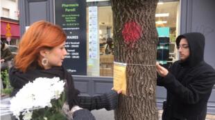 Ariane et Alexandre du collectif Les Morts dans la Rue fixent leur affiche sur les arbres pour demander des renseignements sur des SDF décédés.