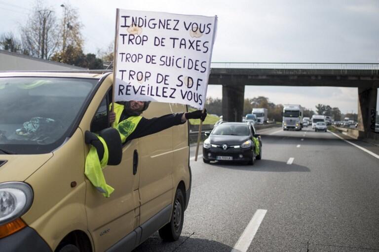Un gilet jaune brandit une pancarte sur la rocade de Rennes (Bretagne), le 20 novembre 2018.