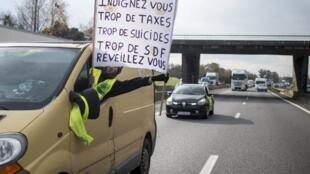 """Manifestante exibe cartaz com os dizeres """"Indignai-vos: muitos impostos, suicídios e sem-teto. Acorde!"""""""