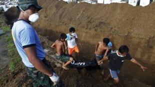 Policiais e voluntários depositam corpos em uma fossa comum em Tacloban City.