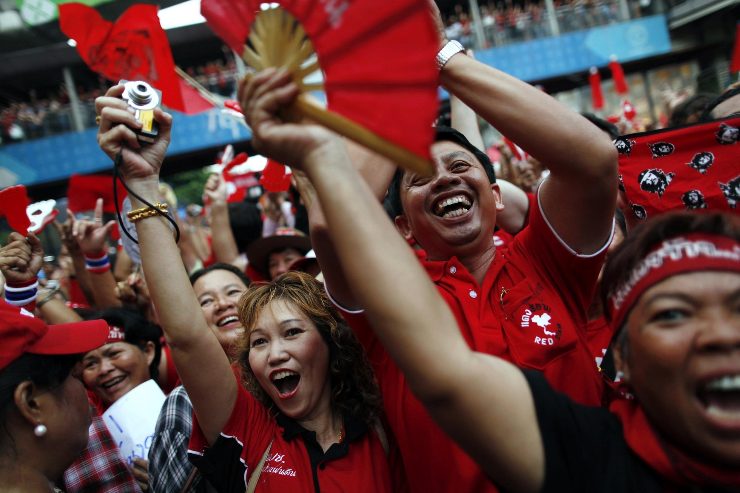 Thai anti-government Red Shirt protesters react as their leader speaks