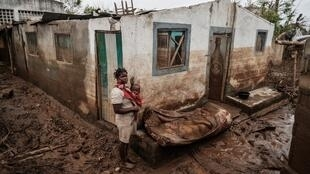 Rosa Tomás e o seu filho Dionísio Eduardo, junto ao que restava da sua casa após a passagem do ciclone Idai em  Março de 2019. Buzi, Moçambique.