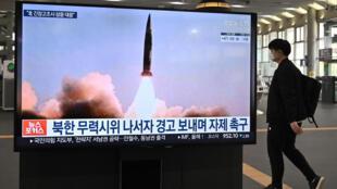 Un homme passe près d'un écran diffusant les tests de missiles, à Séoul, le 26 mars 2021.