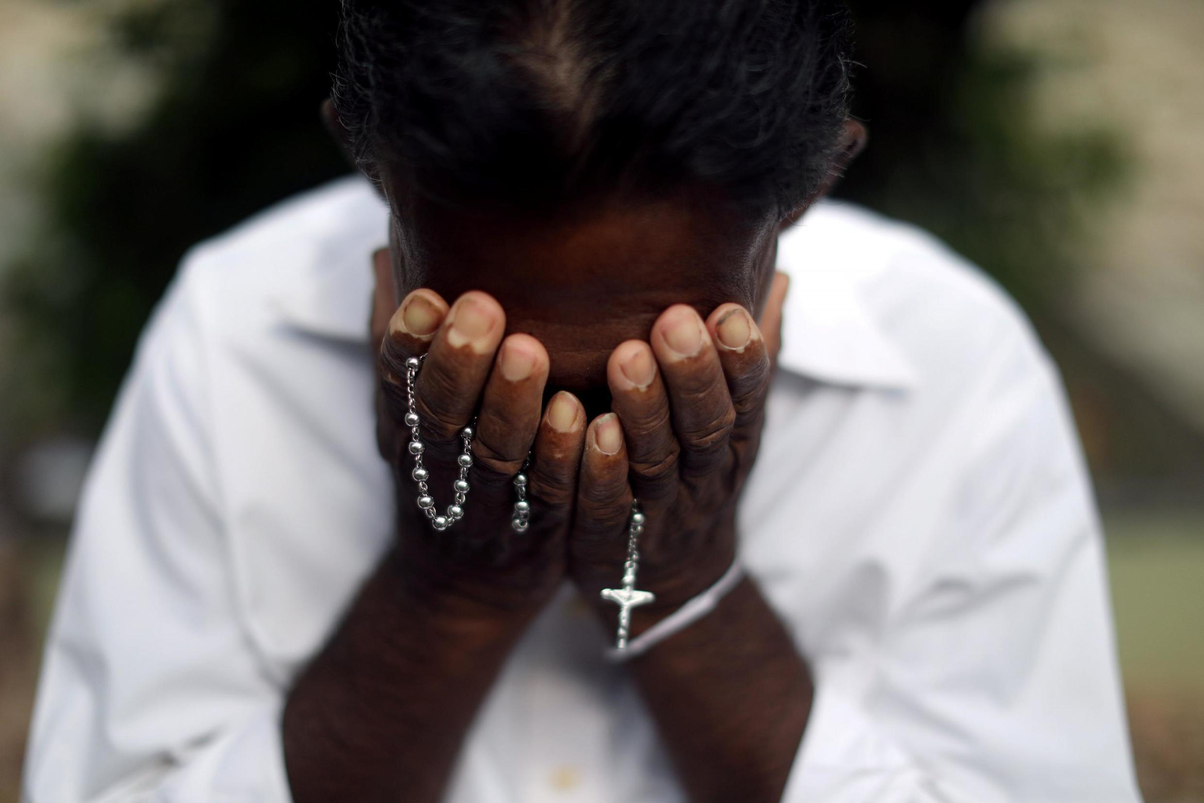 A person mourns at a grave of a victim, two days after a string of suicide bomb attacks on churches and luxury hotels across the island on Easter Sunday, at Sellakanda Catholic cemetery in Negombo, Sri Lanka April 23, 2019.