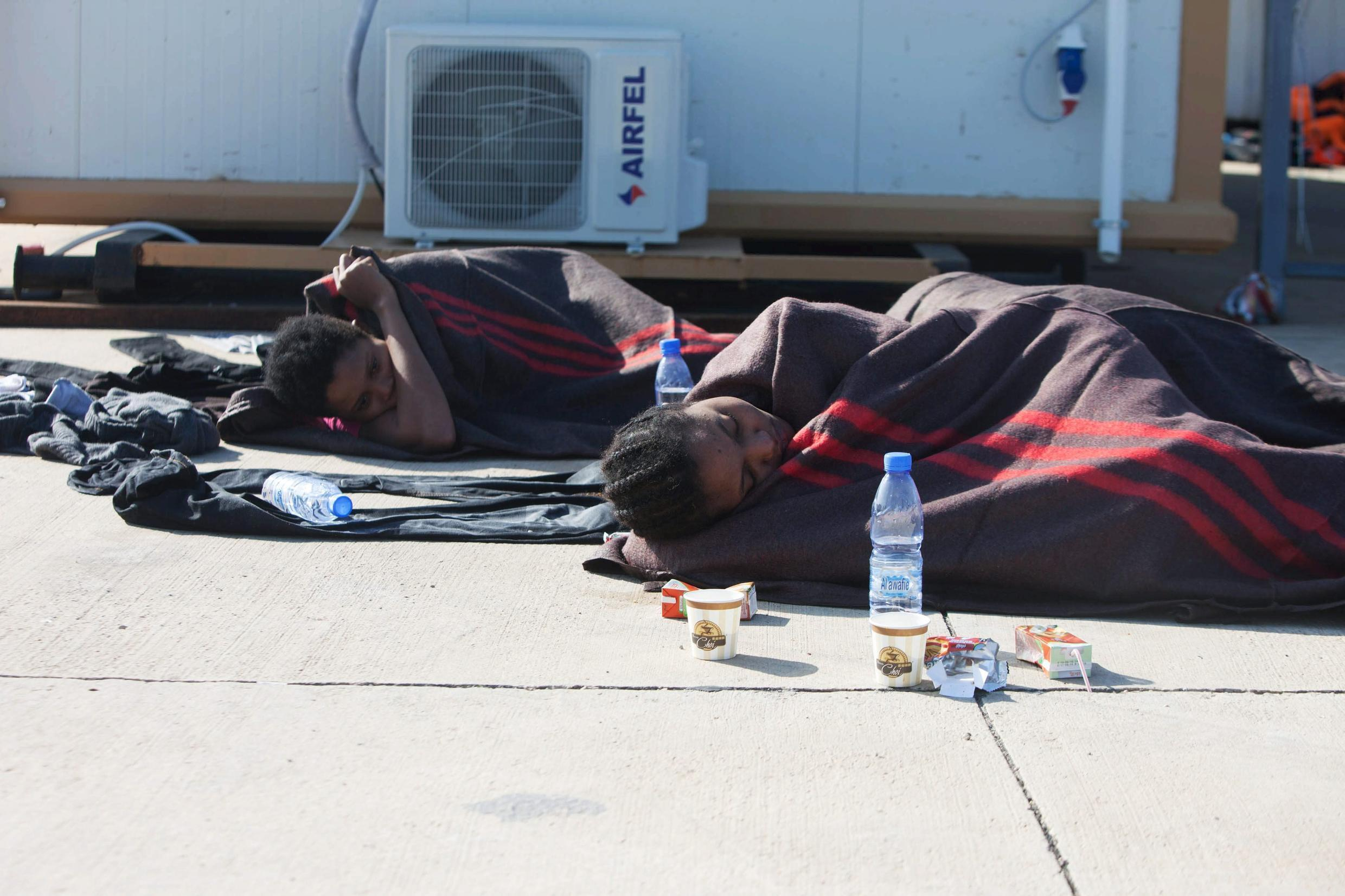 Migrants lay in a navy base, after a boat sank off the coast in Tripoli on 21 December, 2015.