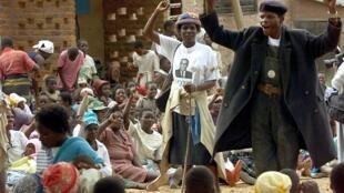 Un squatter (R) amène les ouvriers agricoles à chanter des louanges pour le parti Zanu PF le 6 mai 2000 lors d'une réunion à la ferme de Trianda à 30 km au nord-ouest de Harare.